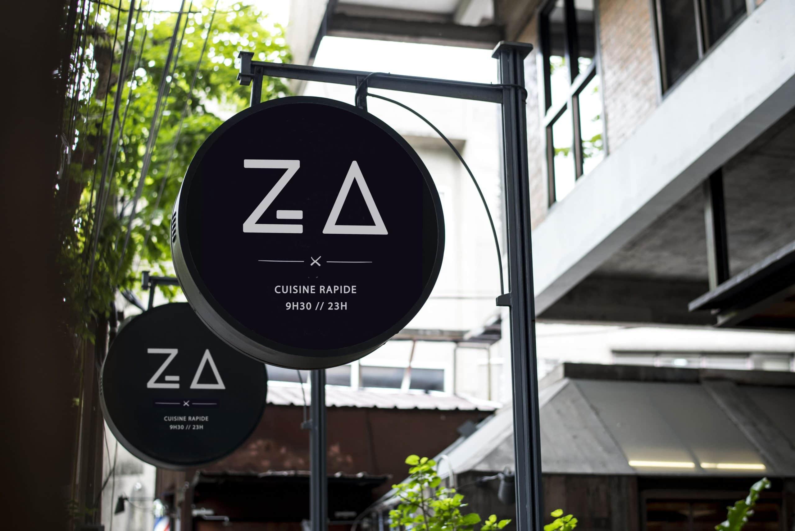 Photo de la devanture du restaurant Za Paris avec le logo blanc dans un encart rond sur fond noir