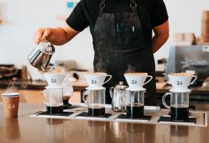 Serveur en train de verser du café dans des tasses ajourées du logo Za Paris