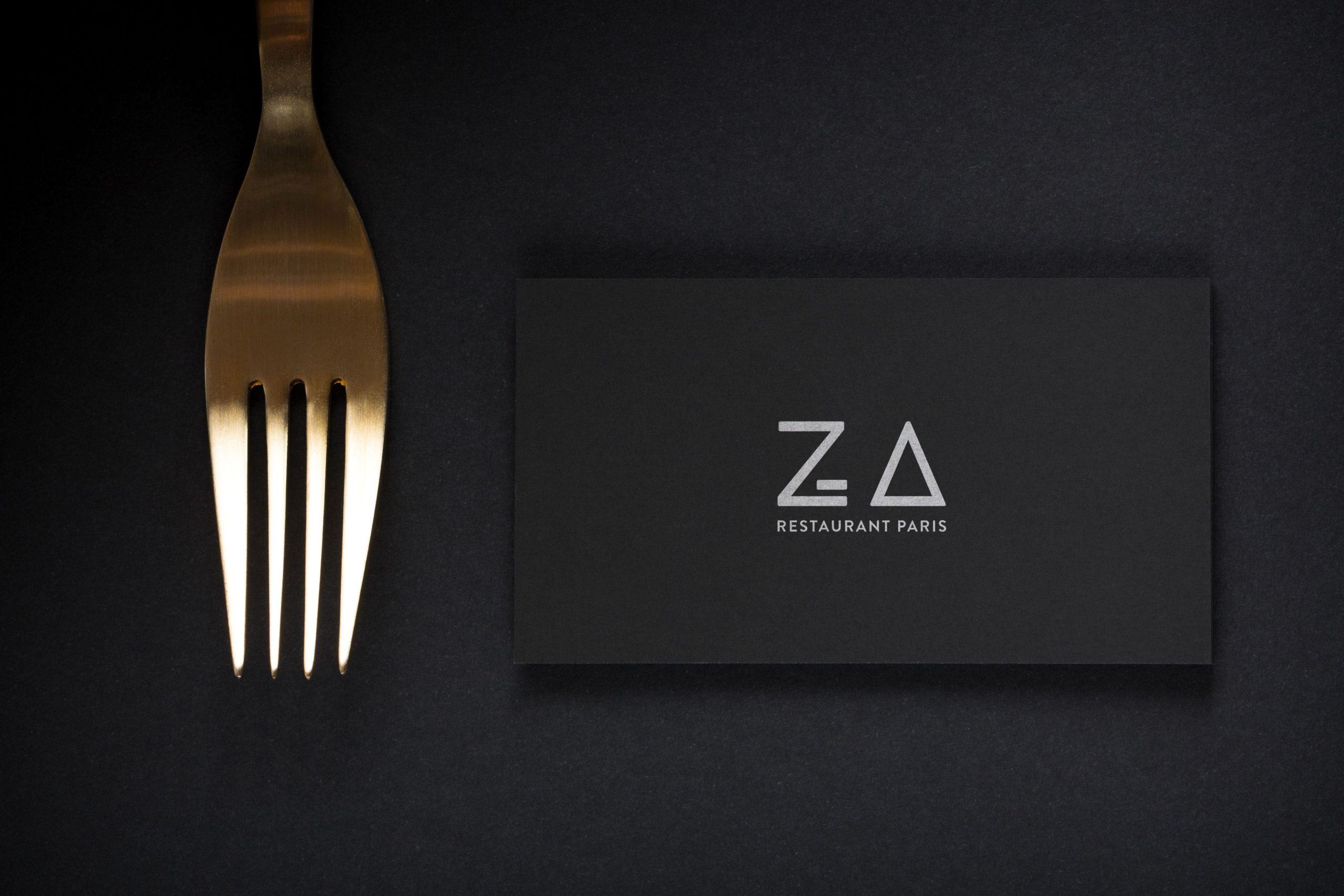 Photo de la carte de visite noir du restaurant Za Paris sur fond noir avec une fourchette posé à côté