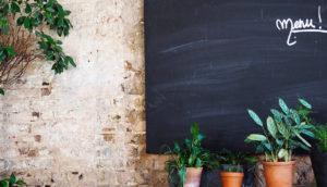 Photo de la cours du restaurant avec une ardoise pour écrire le menu et des plantes