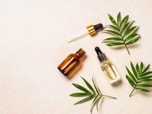 Produit de parfum et feuille verte posé sur un fond beige clair