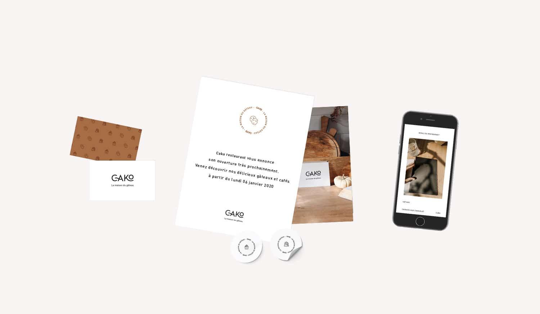 design de deux documents et des cartes de visites réalisé pour le restaurant cako présentés sur un fond beige. On y retrouve également un mobile