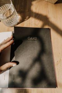 couverture du menu de restaurant noir posé sur une table en bois