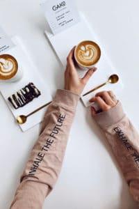 main d'une cliente qui prend son café dans la maison du gâteau Cako