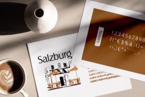 deux feuilles papier sur une table qui présente la typographie Salzburg : les caractères sont écris es uns à la suite des autres