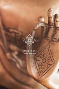 Logo blanc Anastasia Gayatri Ayurveda en arrrière plan on retrouve une photo de bouddha