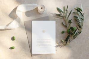 photo de la carte d'invitation pour Anastasia Gayatri Ayurveda. Autour de la carte on y retrouve deux olives, un ruban et une branche de thym