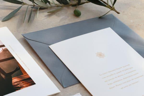 photo de la carte d'invitation pour Anastasia Gayatri Ayurveda. Elle est posée sur une enveloppe grise, autour de la carte on y retrouve une branche de thym et une olive