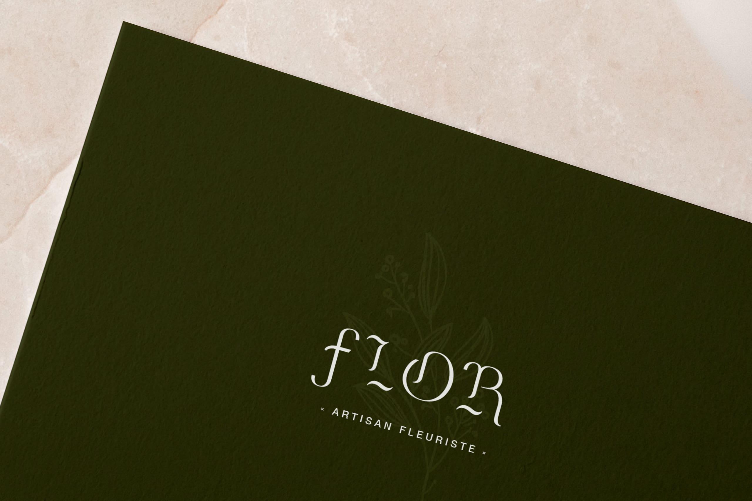 zoom sur une carte de visite du fleuriste Flor. La carte est verte avec le logo en blanc