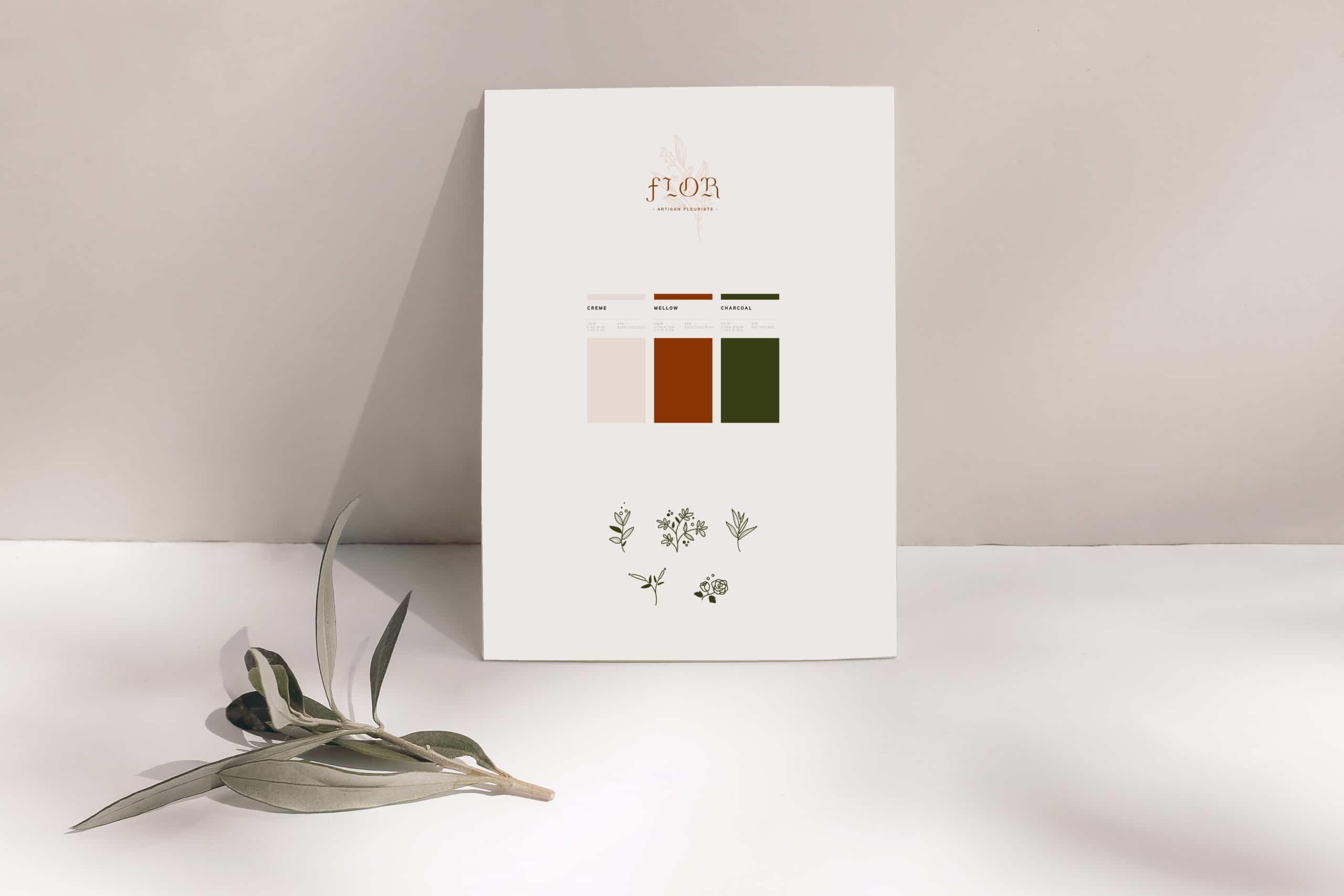 Charte graphique du fleuriste Flor. Feuille blanche posé sur une table avec une feuille posé à gauche. Sur la feuille on retrouve le logotype, les couleurs utilisées et les pictogrammes créés sur-mesure