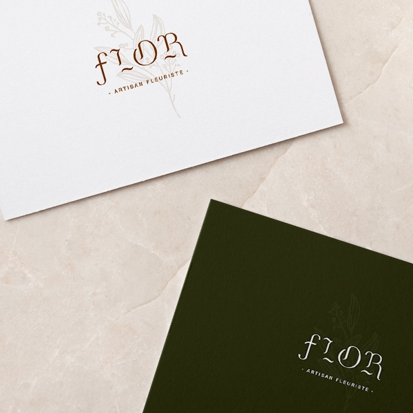 zoom sur les deux cartes de visite du fleuriste Flor. Une carte est blanche avec le logo en beige et l'autre et verte avec le logo en blanc
