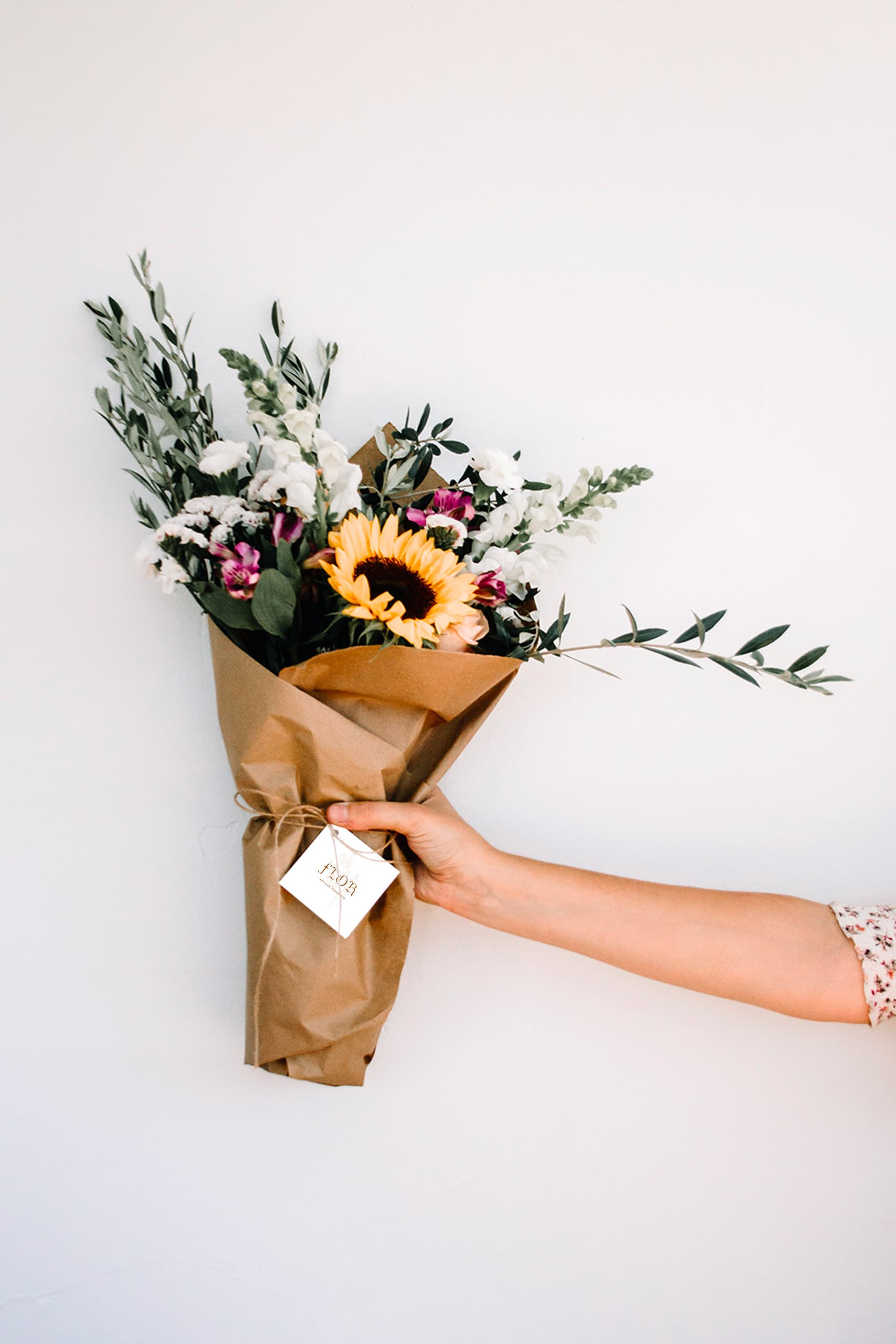 bouquet de fleur tenu par une personne où l'on voi son bras sur la droite. On voit une étiquette avec le logo du fleuriste flor