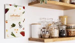 planche du calendrier présentant la couverture générale accrochée sur un mur de cuisine