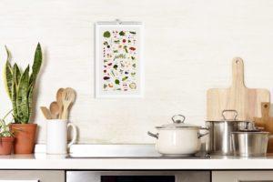 planche du mois de juillet accrochée sur le mur d'une cuisine, on retrouve l'univers de la cuisine avec le four et des spatules en bois