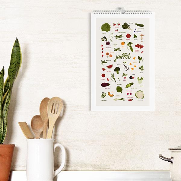 planche du mois de juillet accrochée sur le mur d'une cuisine avec spatules en bois