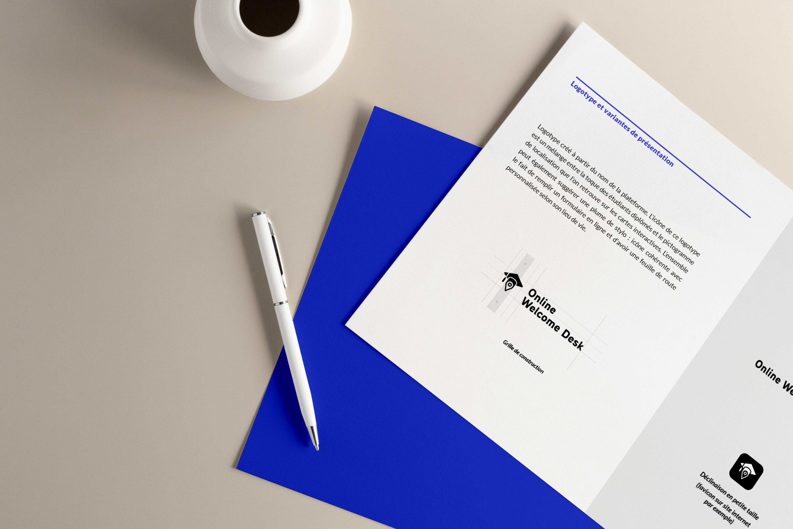 à l'avant de l'image on voit une feuille de papier blanche avec la construction du logotype Online Welcome Desk. À l'arrière on voit une feuille bleu au couleur de la charte graphique