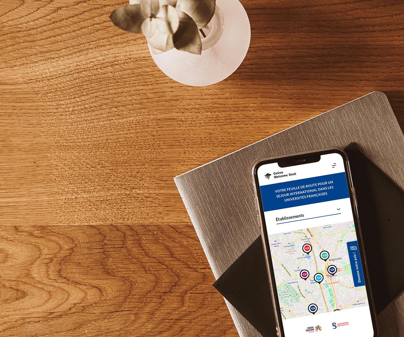 Téléphone portable posé sur un livre et sur une table en bois présentant l'interface responsive de la plateforme Online Welcome Desk