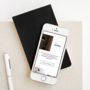 mobile blanc posé sur un cahier et sur une table avec un stylo blanc